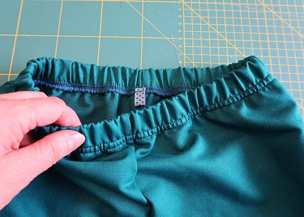 Обработка верхнего среза брюк подгибкой